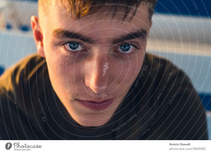 close up portrait of a smiling young man adolescent background beautiful boy candid casual caucasian closeup confident cool cropped dark evening eyes facade