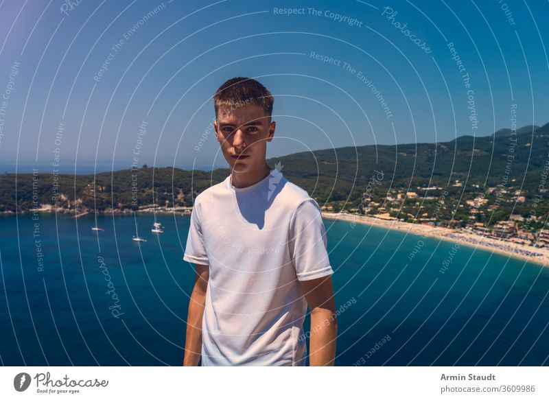 portrait of a self-confident young man with the beach of the city of parga in the background beautiful blue boy casual caucasian cloudless journey lifestyle