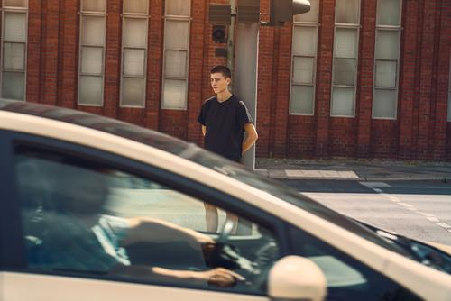 portrait of a lonely young man where a car drives through the picture adolescent beautiful boy building casual caucasian confident culture future issues