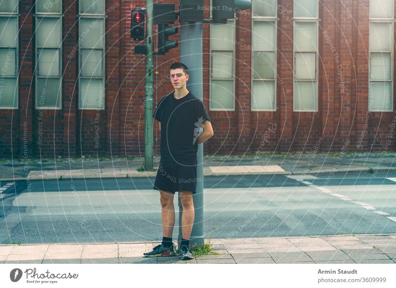 portrait of a lonely young man standing at a red traffic light street adolescent beautiful boy building casual caucasian confident culture future issues