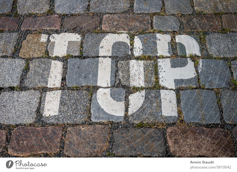 the word top with white color on cobblestone for backgrounds abstract alphabet city closeup design floor grunge hint letters macro mark old outdoor painted road