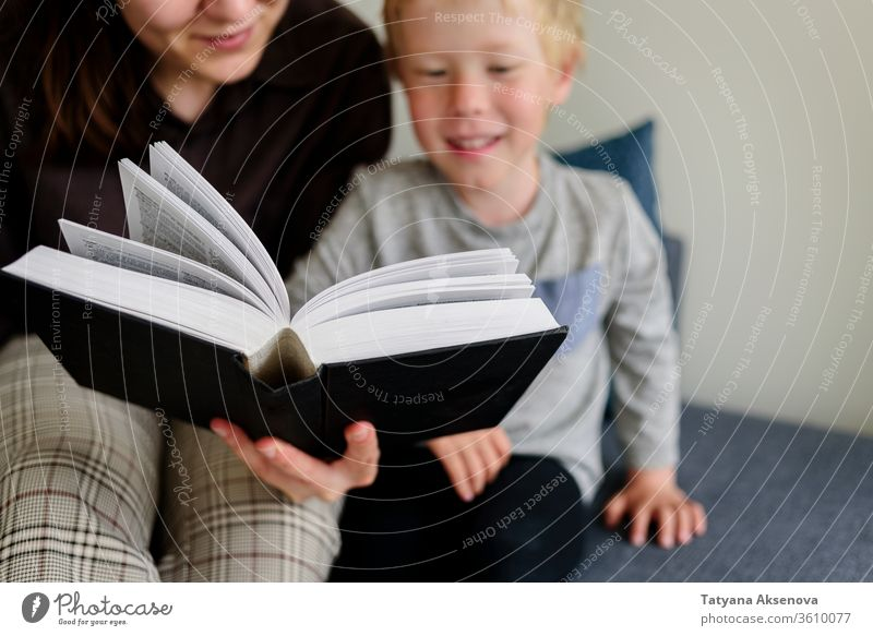 Mother and child reading book and smiling mother family home together happy childhood people parent woman female kid caucasian education happiness indoors mom