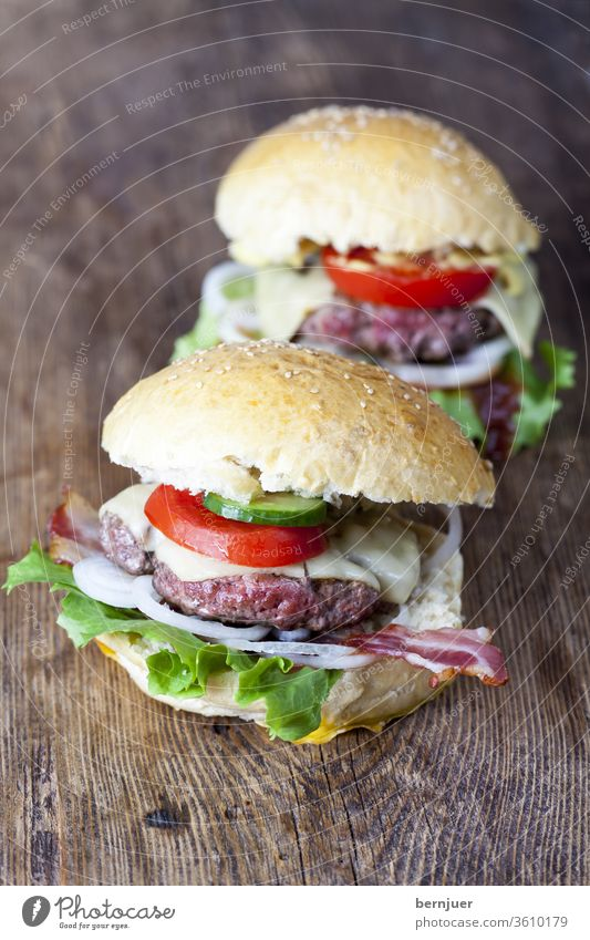 homemade hamburgers on rustic wood Hamburger Juicy two Beef Eating Cheese Lettuce background Meat Delicious American tomatoes White Onion Looking Meal sandwich