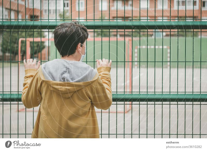 Back view of a sad child looking the football field coronavirus epidemic covid-19 goal playground playtime pandemic quarantine city soccer kid sadness closed