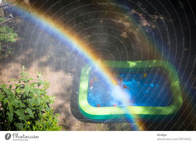 Paddling pool in a garden with rainbow and water drops. Bird's eye view Toys Infancy Rainbow cooling Prismatic colors Drops of water warm season Garden bush