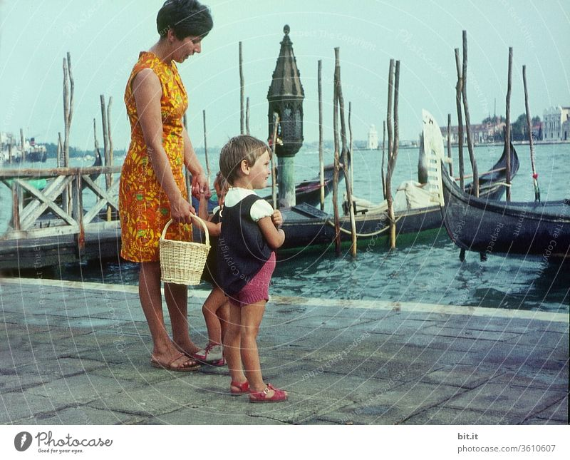 old l Pretty, young, fashionable mother with two daughters on summer vacation, are standing in the port of Venice. Mother with children watches curiously ships and boats in the sea. Family outing in Italy in the 60s. Nostalgic, old 60's family photo