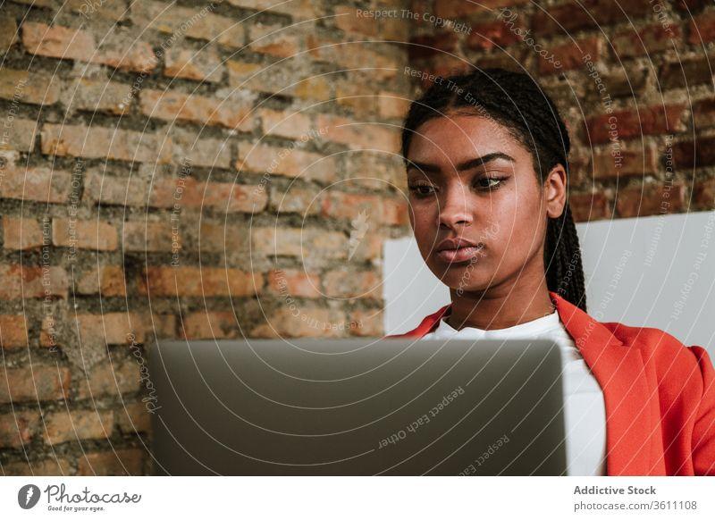 Modern black woman with computer in armchair business laptop online elegant loft design focus interior freelance modern device gadget internet using browsing