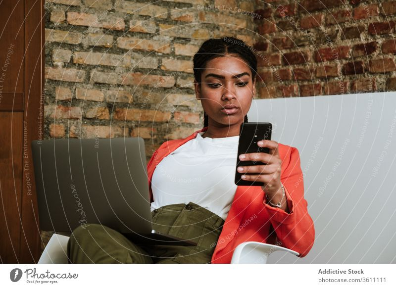 Modern black woman with gadgets in armchair business laptop cheerful smartphone online elegant computer loft design interior freelance modern happy device