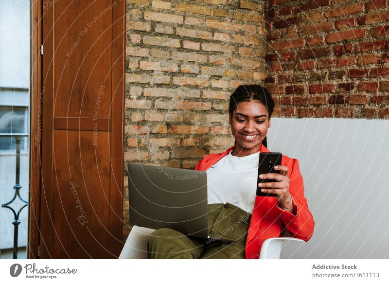 Smiling modern black woman with gadgets in armchair business laptop cheerful smartphone online elegant computer loft design interior freelance happy device