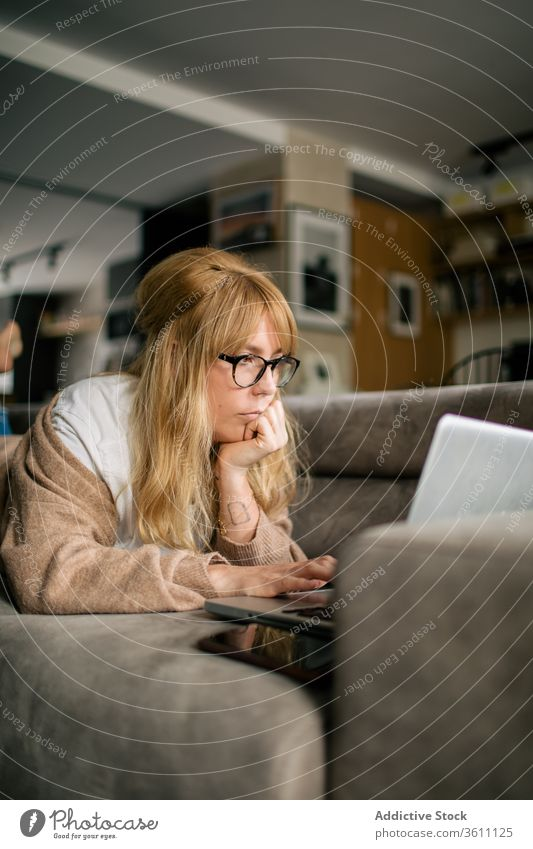 Pensive woman working on laptop at home browsing freelance project using telework lying sofa remote female serious eyeglasses gadget internet device computer