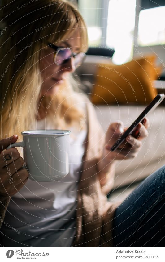 Smiling woman taking selfie on smartphone in living room relax entertain home content photo using smile female soft carpet floor sit cozy cheerful design drink