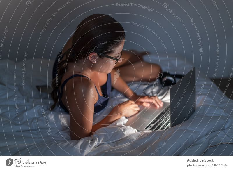 Woman in the computer on bed woman relax using female browsing blanket lying down tank top device technology laptop gadget rest internet home lady cozy comfort