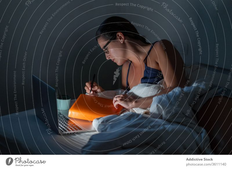 Busy female freelancer working in bed businesswoman night remote laptop browsing using entrepreneur lying down gadget late computer online internet device