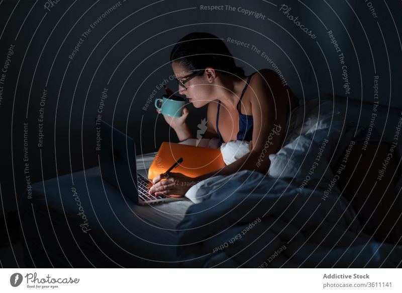 Busy female freelancer working in bed businesswoman night remote laptop browsing drink using coffee entrepreneur lying down gadget computer online internet