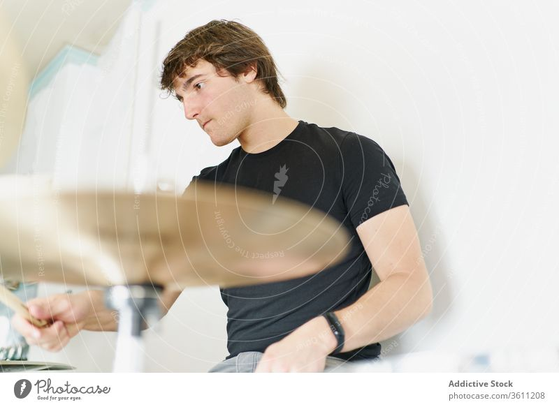 Young man playing on drums kit drumstick perform instrument drummer modern music artist style practice player handsome cool contemporary hobby rhythm expressive