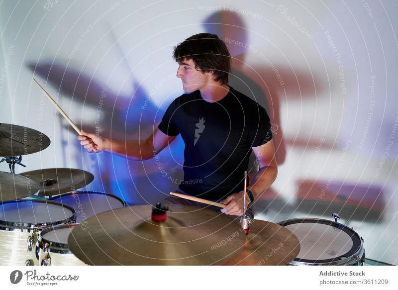 Young man playing on drums kit drumstick perform instrument drummer modern music artist style practice player handsome cool contemporary light hobby rhythm