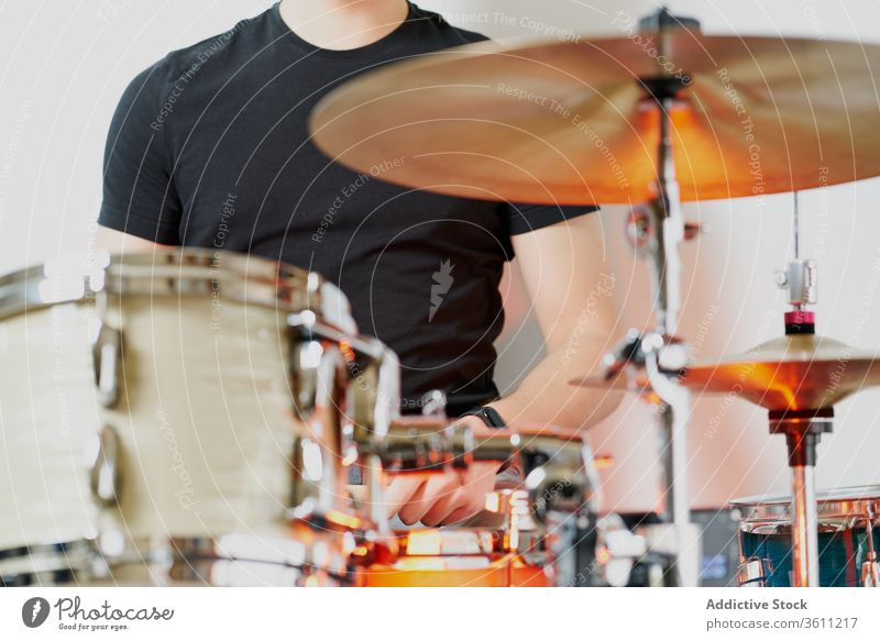 Anonymous young man playing on drums kit drumstick perform instrument drummer modern music artist style practice player handsome cool contemporary hobby rhythm
