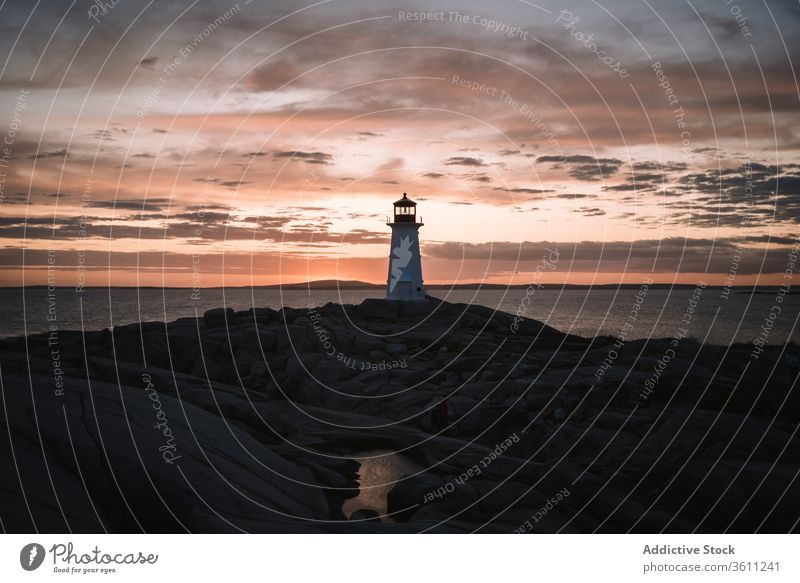 Lighthouse against cloudy sundown sky lighthouse sea shore sunset water evening peggys cove canada dusk twilight ocean coast nature weather idyllic scenic