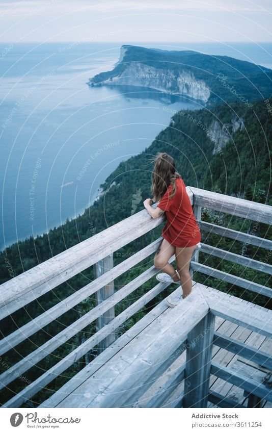 Woman on high terrace against seashore in sunset light woman lookout railing twilight ocean deck alone harmony national park evening la mauricie quebec canada