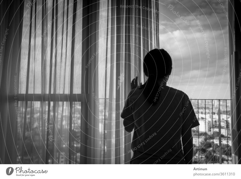 Sad adult Asian woman looking out of window and thinking. Stressed and depressed young woman. Despair women with long hair and T-shirts standing by the window of home or hospital. Lonely and anxiety.