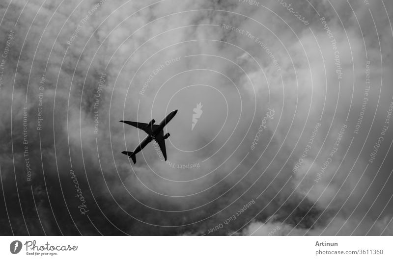 Commercial airplane on grey sky and clouds with copy space. Failed vacation. Hopeless and despair concept. Moody sky and transport plane. Sad emotional scene. Background of aircraft flight.