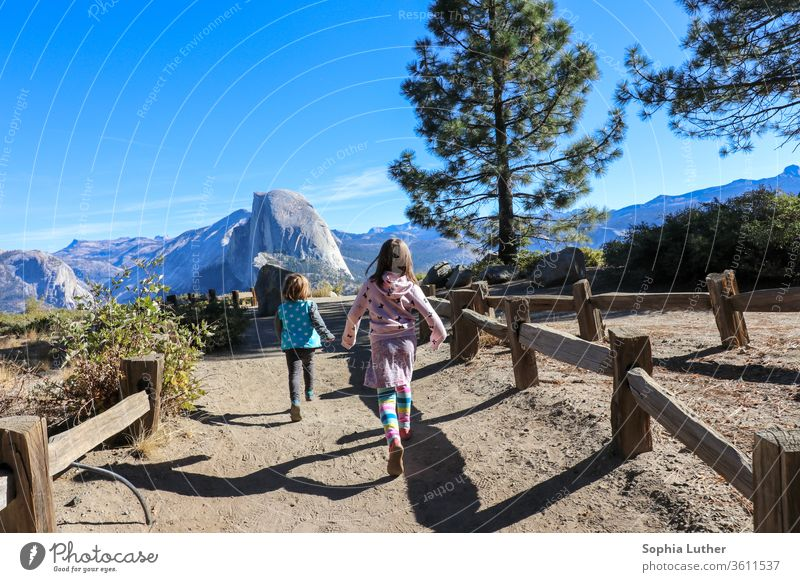 Two children running in the mountains of Yosemite National Park travel parental leave parental leave travel Travel photography Mountain Half Dome Rock girl