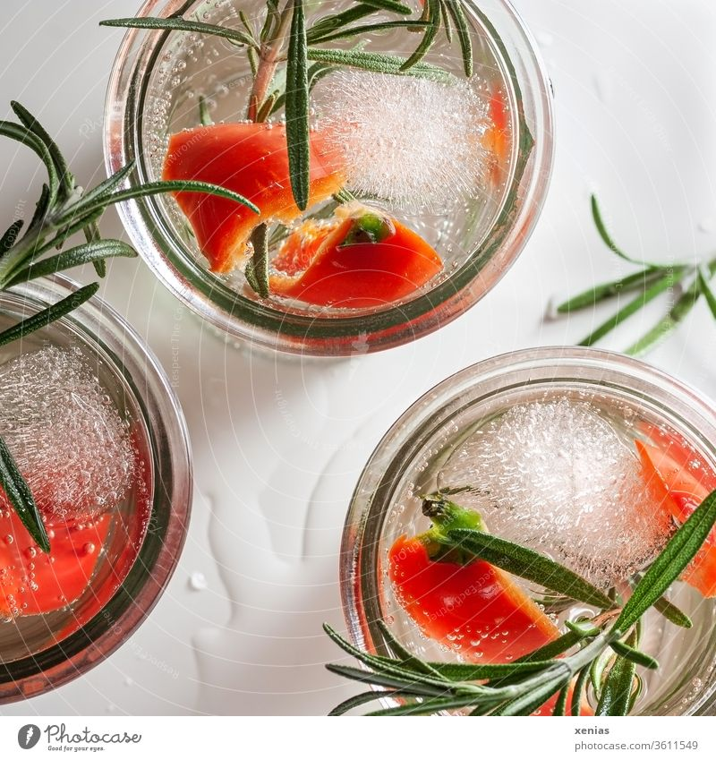 Three glasses of piquant cold soft drink with red pepper, rosemary and ice cubes Beverage Cold drink detox Pepper Rosemary Ice cube three vitamins Refreshment