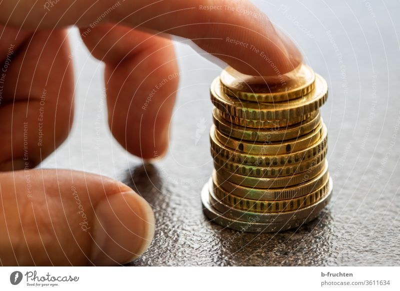 A stack of Euro coins Stack Money Loose change Coin Paying Save Income Financial Industry Economy investment by hand Fingers Forefinger stop Close-up savings
