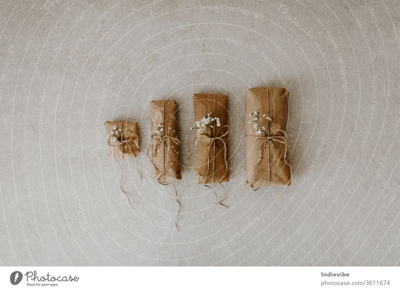 Four gift wrapped in paper with dried flower and string on marble background. Zero waste wrapping idea for Christmas, birthday. Reusable package with hemp string.