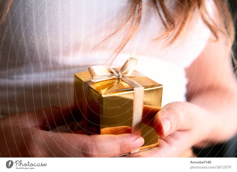 Women's hands holding gold gift box, Holiday present,birthday,Christmas, Father or Mother's, Valentine's day close-up christmas background family woman business