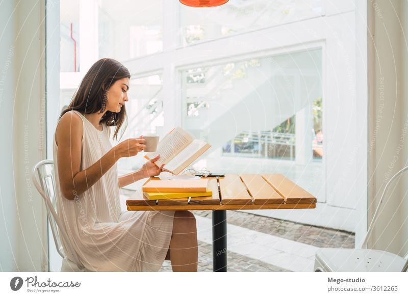 Young woman reading a book at coffee shop. female sitting relaxing hobby serious culture coffee break caucasian looking pensive textbook portrait learn