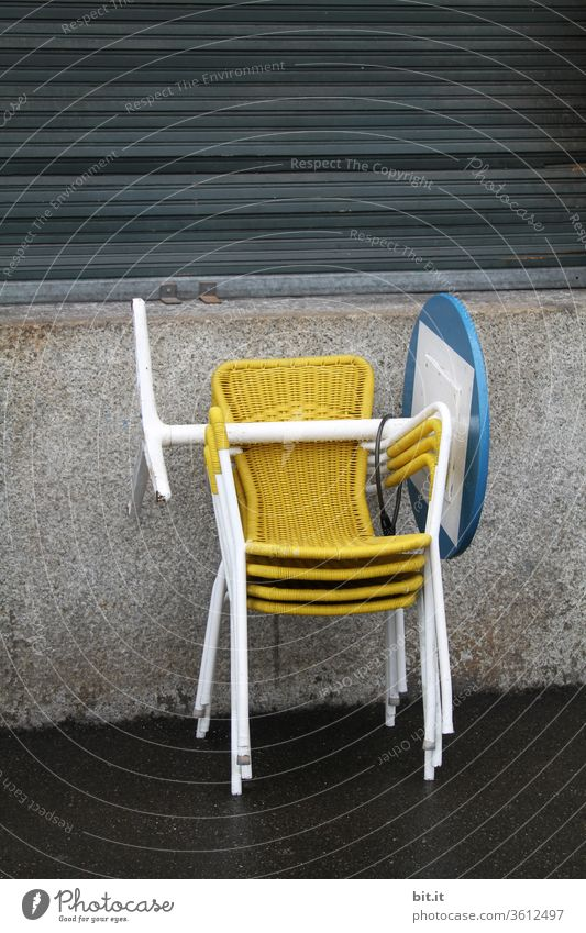 Yellow, gaudy, trendy plastic bistro chairs are stacked on top of each other, in front of a grey, dreary house wall, with closed shutters. End of work, end of season in a street café with furniture, chairs and blue, round bistro table stacked on top of each other. To
