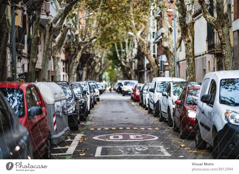 Frontal view of a city street with cars parked on both sides road building modern district vehicle town architecture urban transport exterior way auto nobody