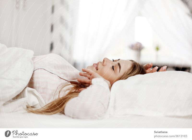 A young smiling beautiful girl is lying in bed in the bedroom. The girl stretches in the morning after waking up. Side view, space for text eyes closed indoors