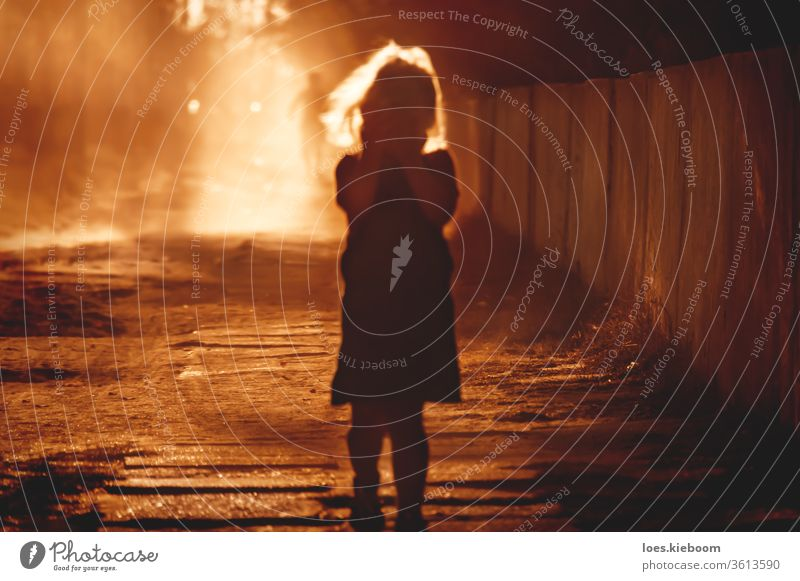 Defocused silhouette of a child covering her face with the hands and blurred person running into light at in the back abuse violence victim girl cry space fear