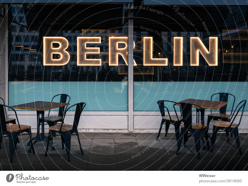 Café with illuminated Berlin lettering, evening light Sidewalk café chairs tables Empty Gastronomy Restaurant Exterior shot Tourism Street Lifestyle rainy