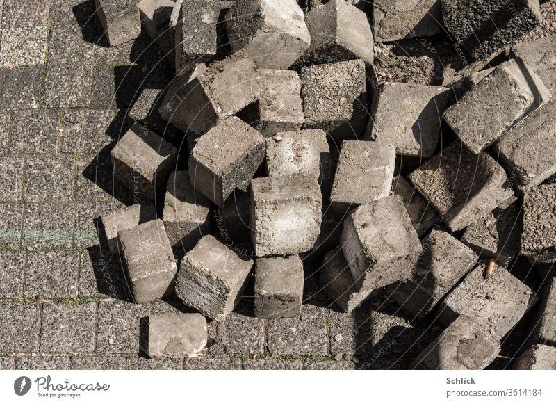 Loose concrete paving stones in heaps Paving stone Heap loose Concrete Construction site Vandalism Force Demonstration Riots cubes Cuboid Cigarette Butt off