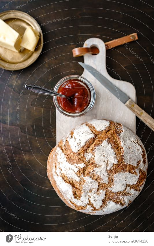 A loaf of bread, a glass of jam and butter on a golden plate, rustic style Bread Jam Butter Breakfast Plate Chopping board plan Food baked Delicious Sweet Fresh