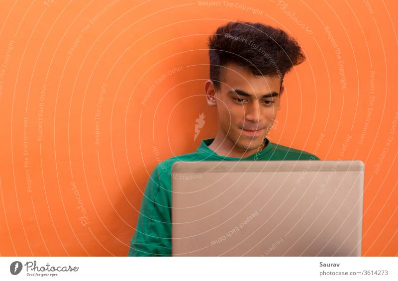 Young Man smiling while talking to someone on his laptop. millennial isolation young man indoors chatting entertainment stay connected communication video call