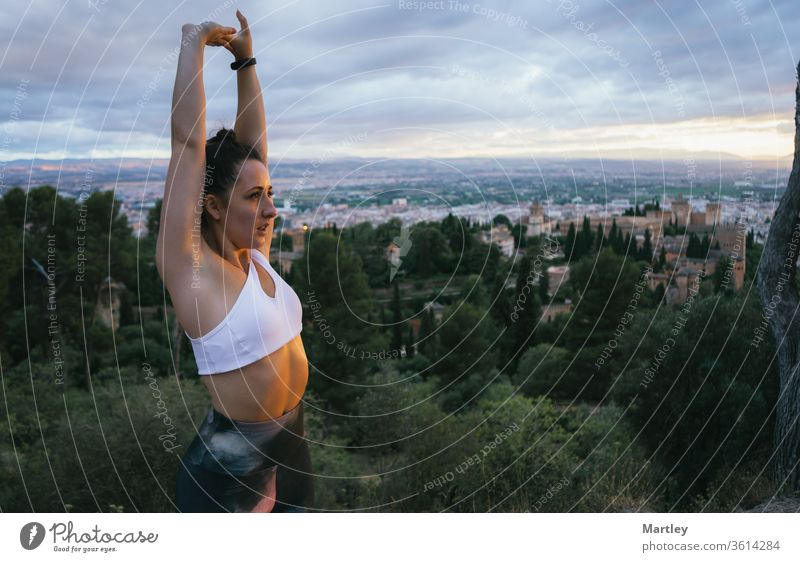 Fit young woman doing stretching exercises over the Alhambra city in Granada at sunset in summer. Pretty girl relaxing in nature after doing sports. fitness