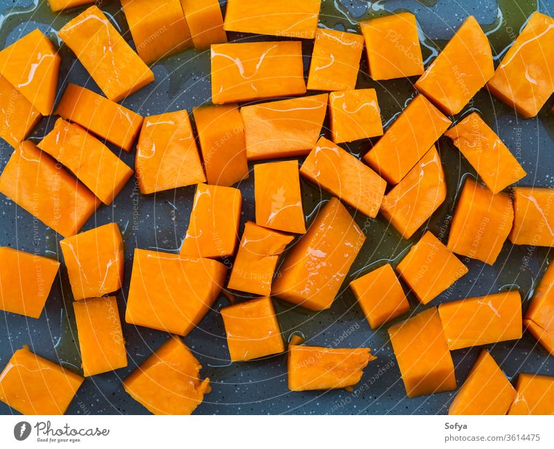 Chopped pumpkin drizzled with oil for baking squash food chop cut pour olive board wooden rustic cooking healthy kitchen fresh vegetable knife vegetarian slice