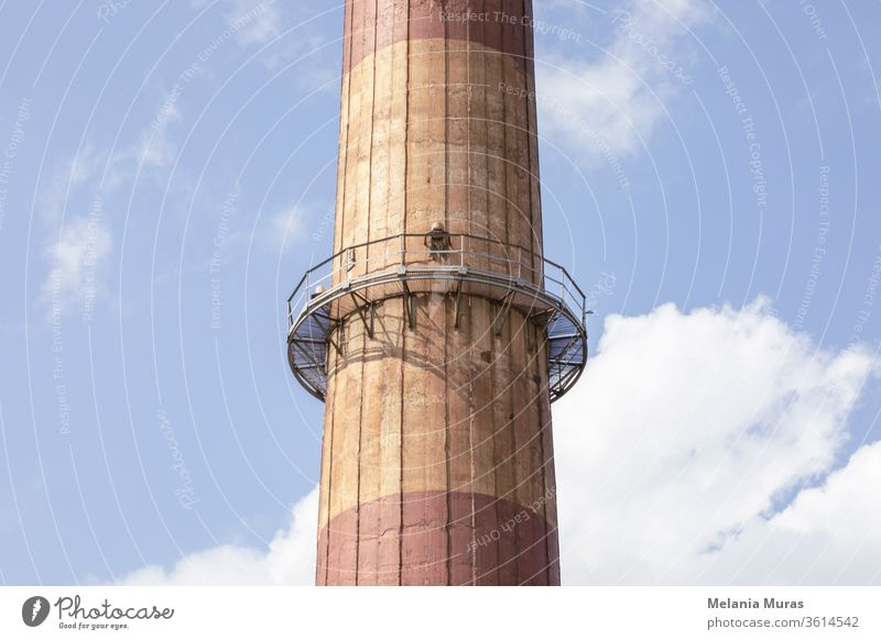 Part of old high industrial chimney with metal construction. Close up. Blue sky background. Old industrial architecture. Coal industry. Chimney Architecture