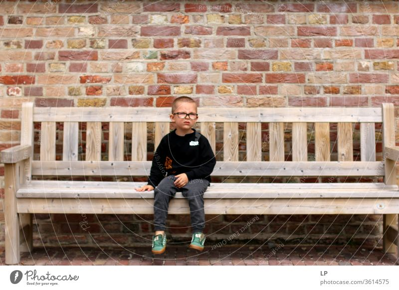 boy sitting down on a bench Loneliness loner Individual alone bank Middle center Separate distressed upset Abandoned Deserted Education Punish waiting time