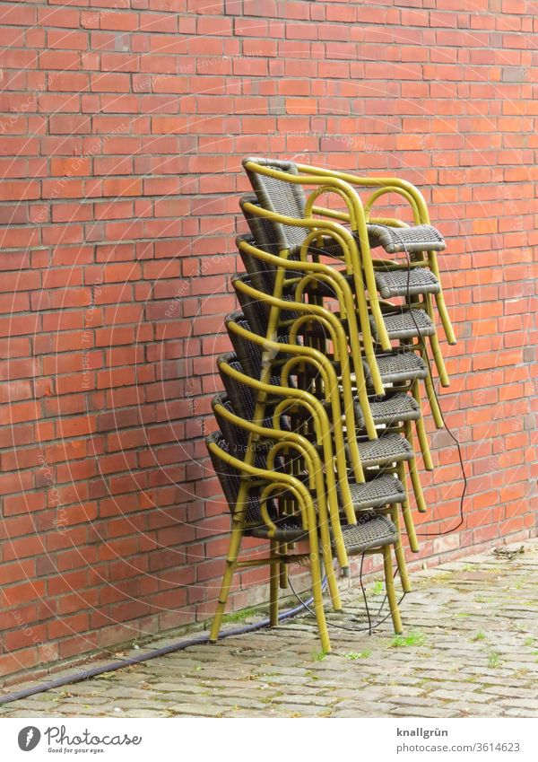 Eight secured basket chairs stacked one on top of the other in front of a red-brown brick wall Chair Stack Restaurant corona crisis Deserted Exterior shot