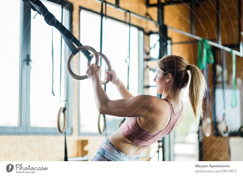 Young sporty woman training on gymnastic rings muscular arms holding indoor fit fitness tough endurance one people focused power young blonde workout strength