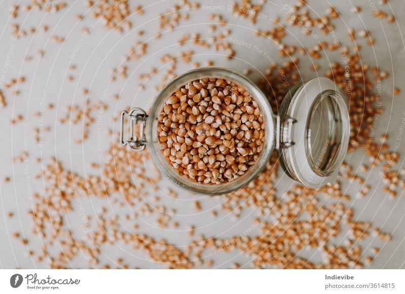 Organic corn seeds and a glass jar container on a grey background food brown isolated grain ingredient dry cereal healthy organic heap white vegetarian raw