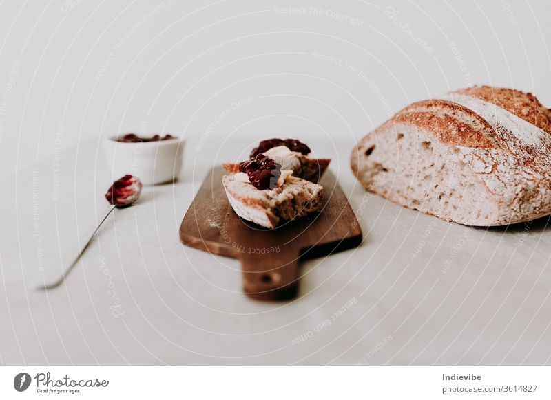 Two slice of home made organic sourdough bread slice with butter and raspberry jam on a wooden chopping board with spoon and loaf of bread and napkin fresh