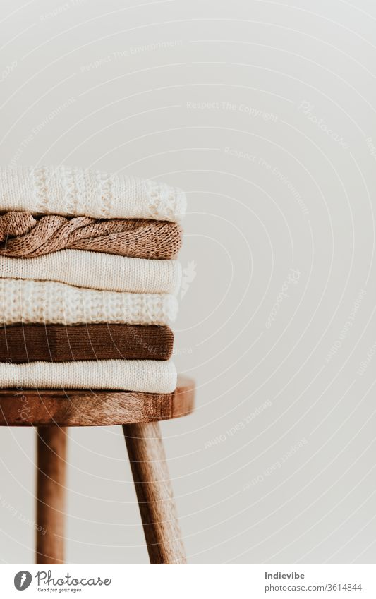 Women fashion composition. Warm winter female woollen knitted sweaters, pullovers stack on a wooden stool at white background. Modern clothes concept for magazine, blog, social media.
