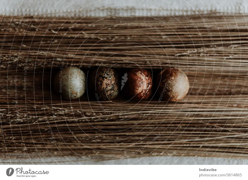 Four different pattern natural dyed egg easter decoration on straw background on a linen tablecloth organic concept top view seasonal tradition homemade nature