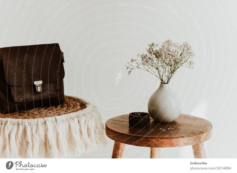 Accessory composition detail for women and girls. White flower in a small ceramic vase with copper bracelet and golden rings and leather bag on a wooden side table at a white wall in a bright room.